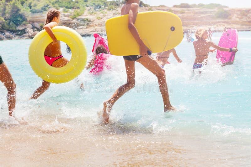 Grupo de crianças que correm no mar para nadar fotos de stock