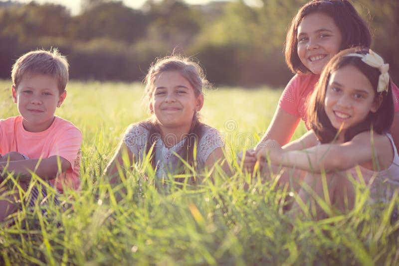 Grupo de crianças que descansam no acampamento fotos de stock royalty free