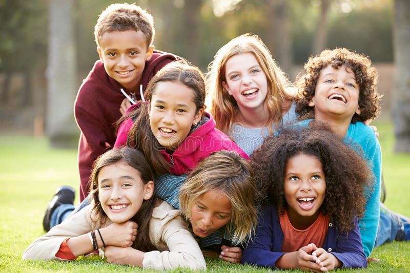 Grupo de crianças que encontram-se na grama junto no parque fotos de stock