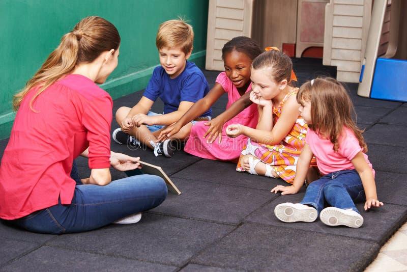 Grupo de crianças que falam sobre o livro no pré-escolar fotos de stock royalty free