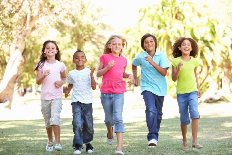 Grupo de crianças que funcionam através do parque imagem de stock royalty free
