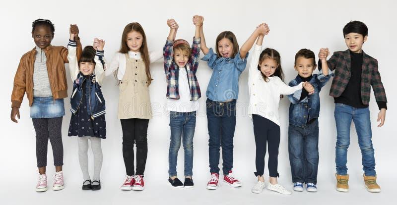 Grupo de crianças que guardam a felicidade da expressão da cara das mãos que sorri sobre imagem de stock