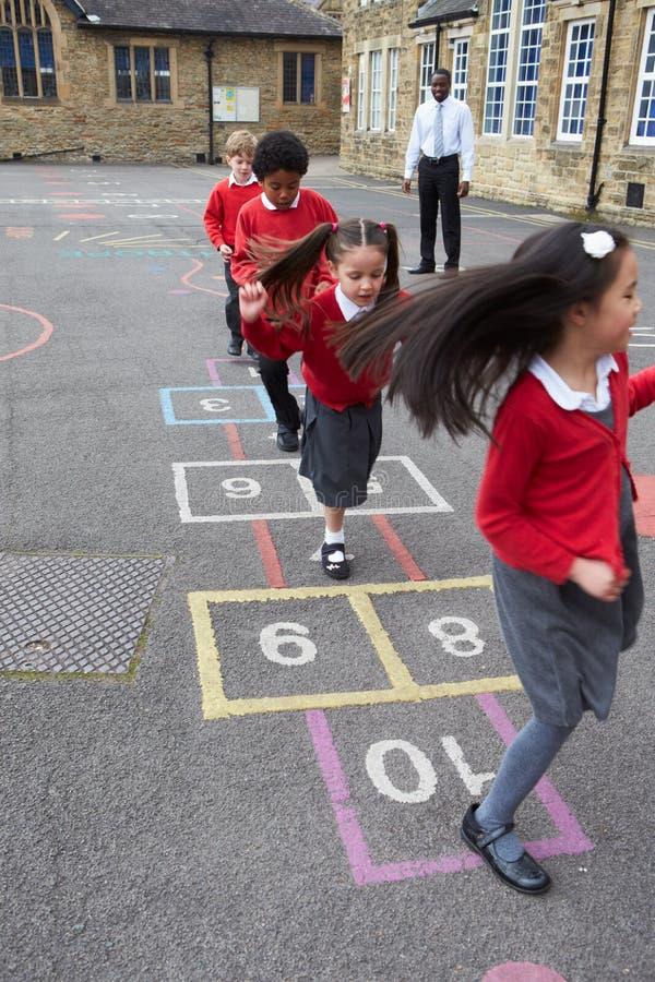 Grupo de crianças que jogam amarelinha no campo de jogos da escola imagens de stock