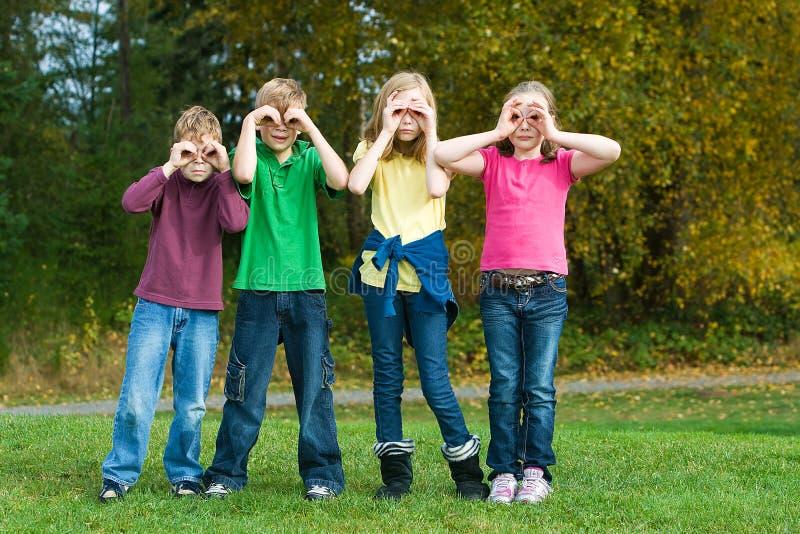 Grupo de crianças que jogam com binocular imaginário foto de stock