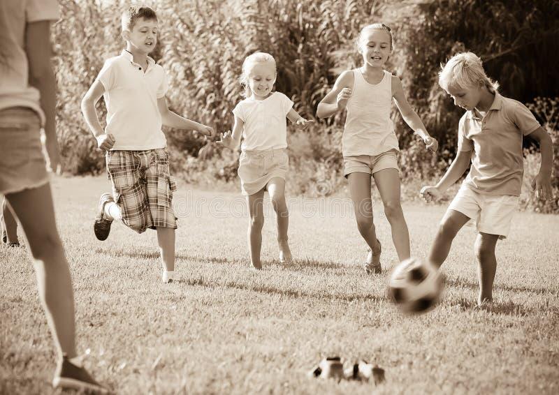 Grupo de crianças que jogam o futebol junto no gramado verde no parque imagem de stock