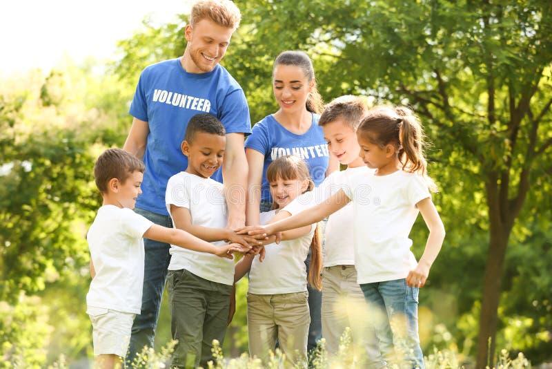Grupo de crianças que juntam-se às mãos com voluntários imagens de stock royalty free