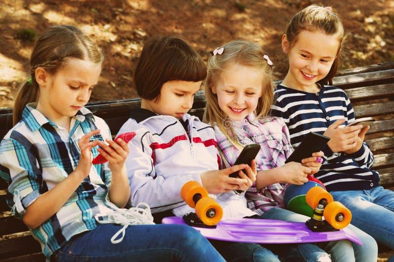 Grupo de crianças que levantam com dispositivos móveis fotos de stock
