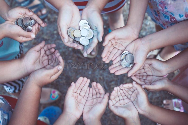 Grupo de crianças que mantêm o dinheiro nas mãos no círculo unido fotos de stock royalty free