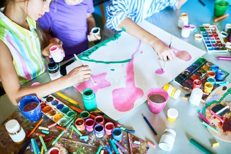 Grupo de crianças que pintam junto foto de stock