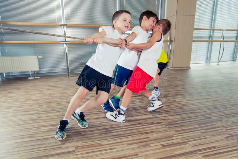 Grupo de crianças que puxam uma corda na sala da aptidão imagem de stock royalty free