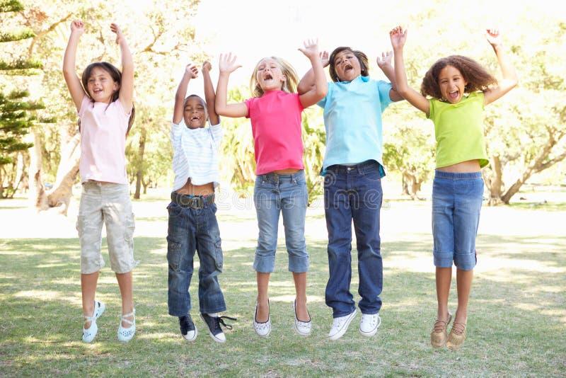 Grupo de crianças que saltam no ar no parque imagem de stock