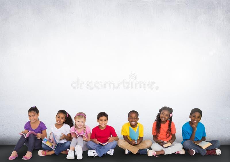 Grupo de crianças que sentam-se na frente do fundo cinzento vazio fotografia de stock royalty free