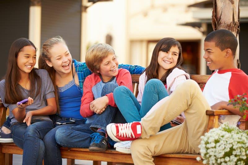 Grupo de crianças que sentam-se no banco na alameda imagem de stock