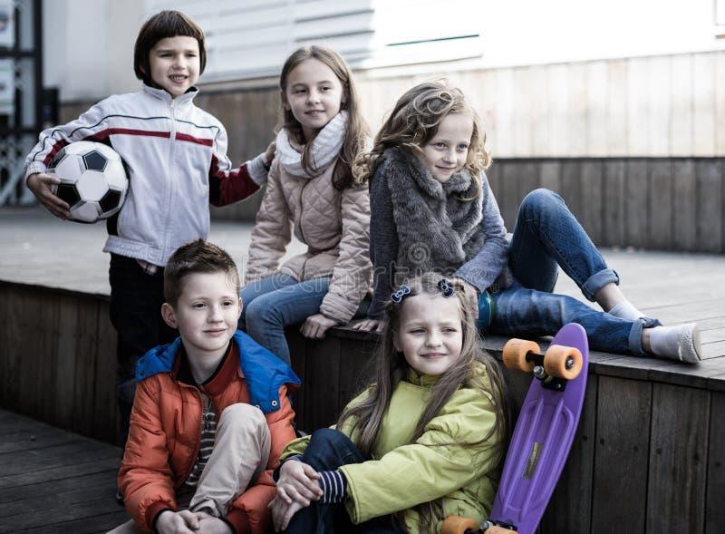 Grupo de crianças que sentam-se no recreio de madeira do andaime foto de stock