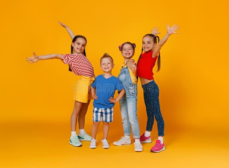 Grupo de crian?as felizes alegres no fundo amarelo colorido fotografia de stock