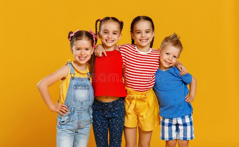 Grupo de crian?as felizes alegres no fundo amarelo colorido imagens de stock royalty free