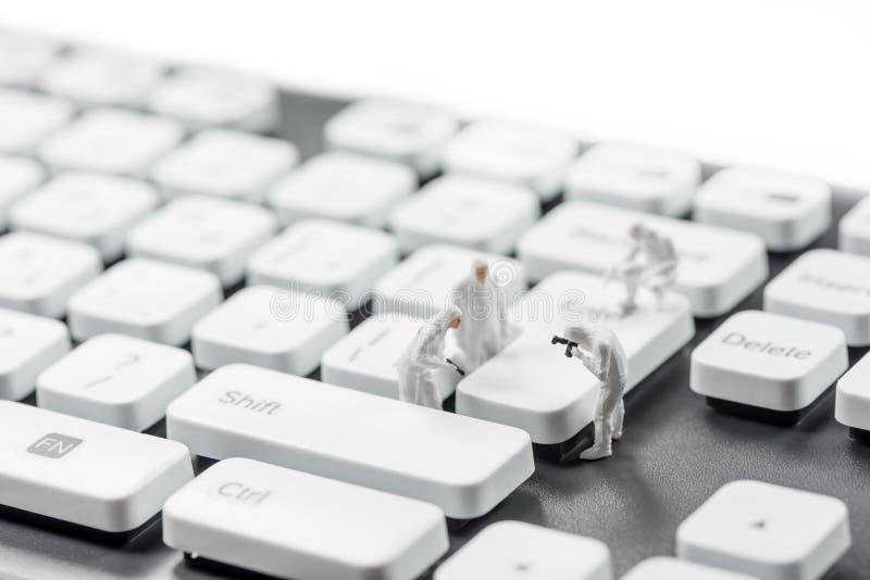 Grupo de criminalists diminutos que inspecionam o teclado de computador Conceito do cibercrime fotografia de stock