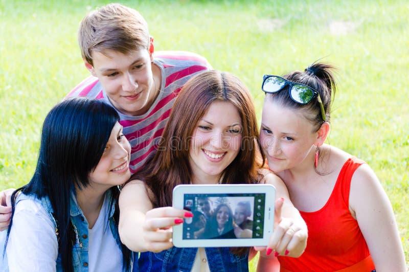 Grupo de cuatro amigos felices de la gente joven del smilng que toman la imagen de ellos mismos con la tableta fotos de archivo