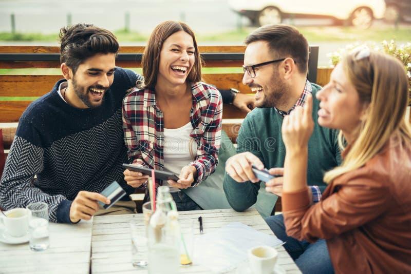 Grupo de cuatro amigos que se divierten un café junto imagen de archivo libre de regalías