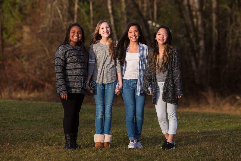 Grupo de cuatro chicas jóvenes bonitas con la tenencia de la diversidad cultural foto de archivo