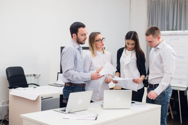 Grupo de cuatro hombres y mujeres diversos en ropa informal que hablan en oficina fotos de archivo