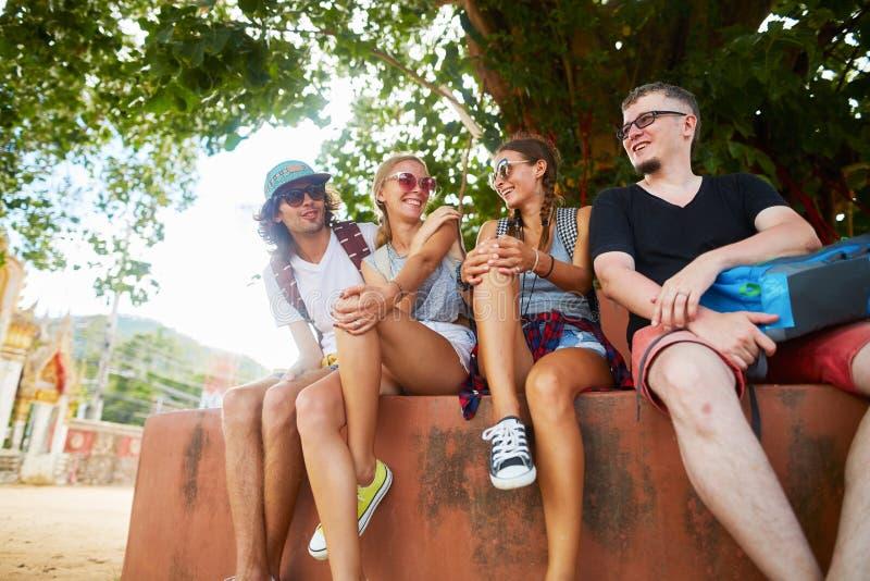 Grupo de cuatro turistas que se sientan debajo de árbol cerca del templo en Tailandia imagenes de archivo