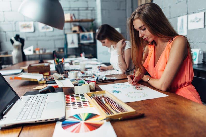 Grupo de desenhadores de moda criativos que tiram esboços dos acessórios que trabalham no estúdio fotografia de stock royalty free