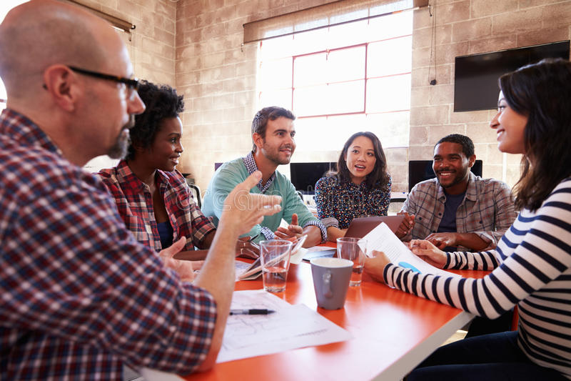 Grupo de desenhistas que têm a reunião em torno da tabela no escritório imagem de stock
