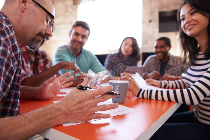 Grupo de desenhistas que têm a reunião em torno da tabela no escritório imagens de stock royalty free
