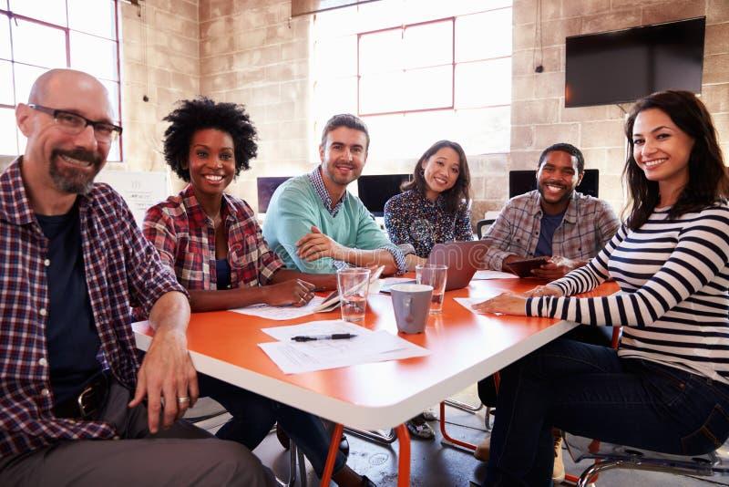 Grupo de desenhistas que têm a reunião em torno da tabela no escritório fotos de stock