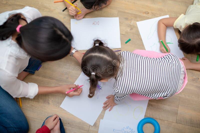 Grupo de dibujo preescolar del estudiante y del profesor en el papel en clase de arte De nuevo a escuela y a concepto de la educa imagenes de archivo