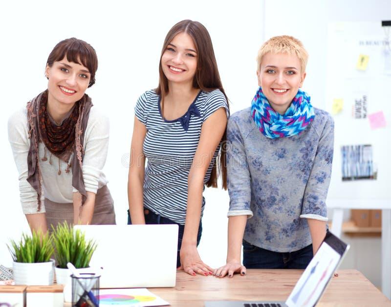 Grupo de diseñadores de moda que discuten diseños en a fotos de archivo