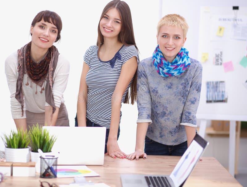 Grupo de diseñadores de moda que discuten diseños en a foto de archivo