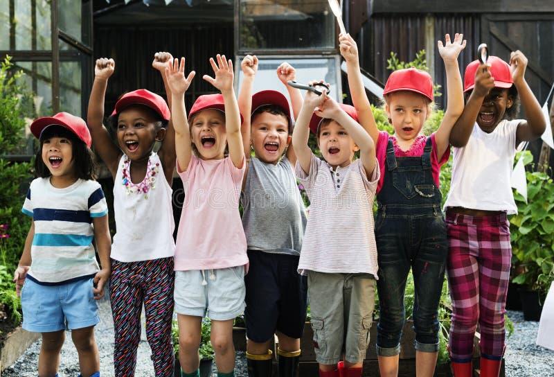 Grupo de disparos al campo de la escuela de los niños que aprende al aire libre smilin activo fotos de archivo