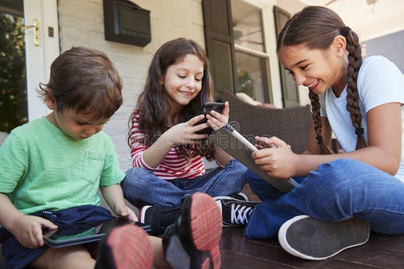 Grupo de dispositivos de Sit On Porch Playing With Digital das crianças foto de stock royalty free