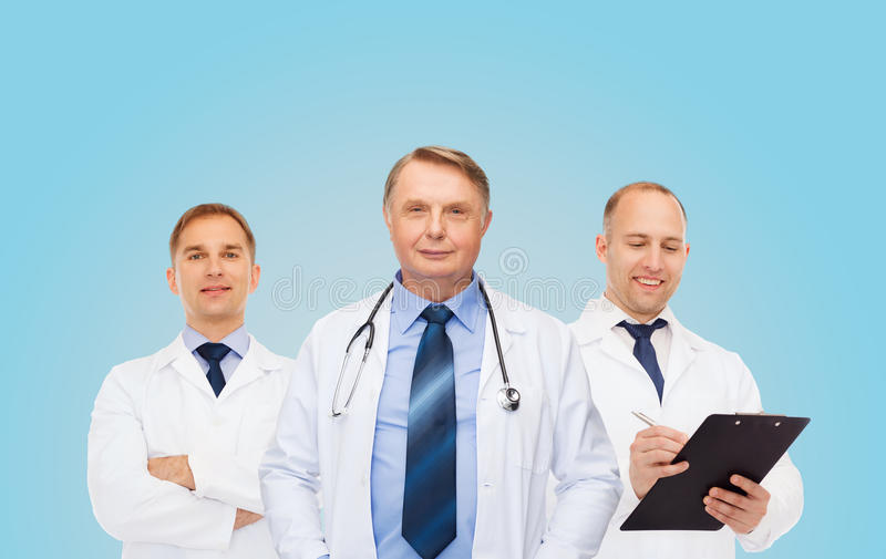 Grupo de doctores de sexo masculino sonrientes en las capas blancas imagenes de archivo