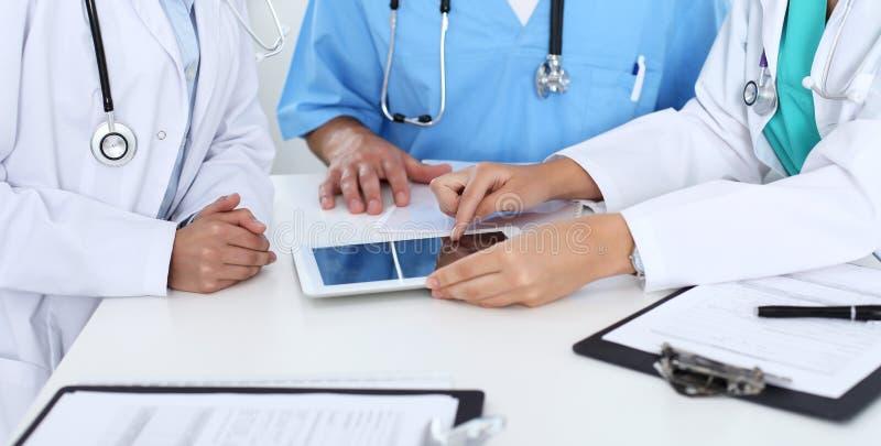 Grupo de doctores en la reunión médica Ciérrese para arriba del médico que usa la almohadilla táctil o la tableta imagen de archivo