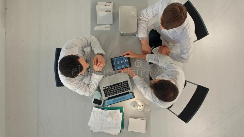Grupo de doctores felices con los ordenadores de la PC de la tableta que se encuentran en la oficina médica Visión superior imagenes de archivo