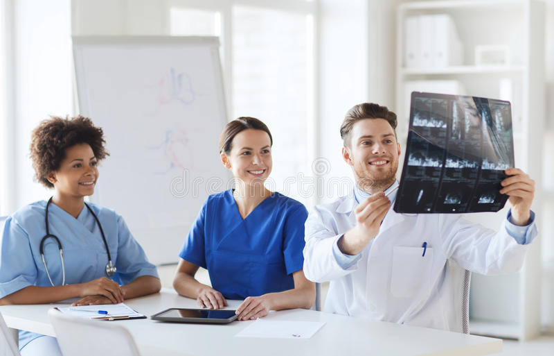 Grupo de doctores felices que discuten imagen de la radiografía fotos de archivo
