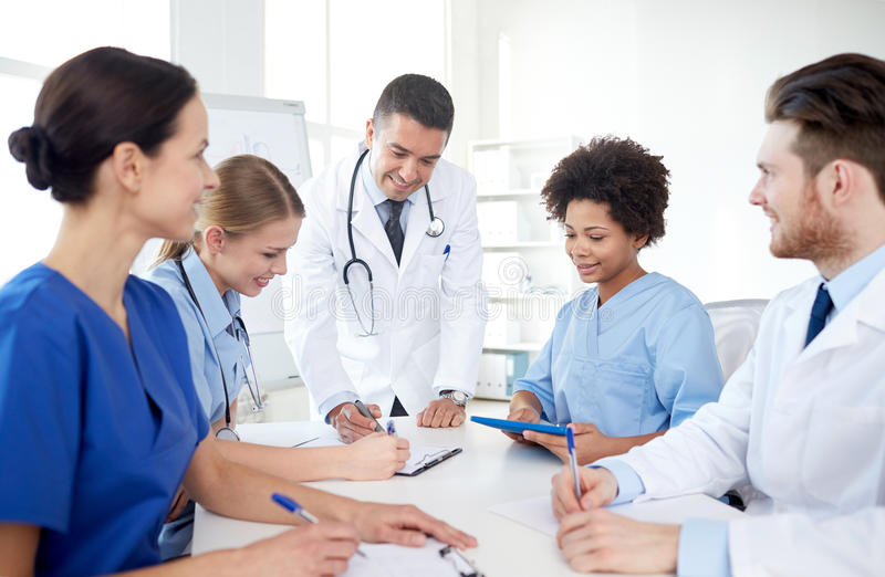 Grupo de doctores felices que se encuentran en la oficina del hospital fotografía de archivo libre de regalías