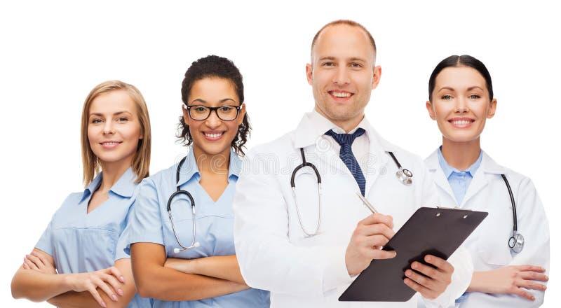 Grupo de doctores sonrientes con el tablero foto de archivo libre de regalías