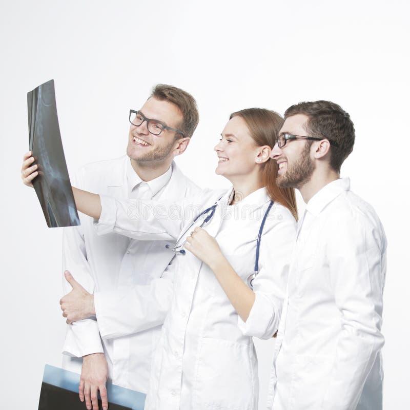 Grupo de doctores sonrientes que discuten radiografías En blanco foto de archivo