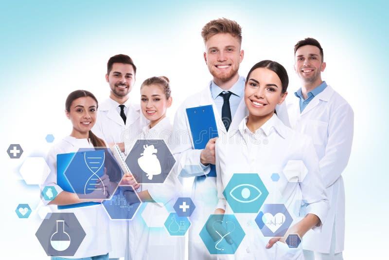 Grupo de doctores y de iconos en fondo ligero fotografía de archivo