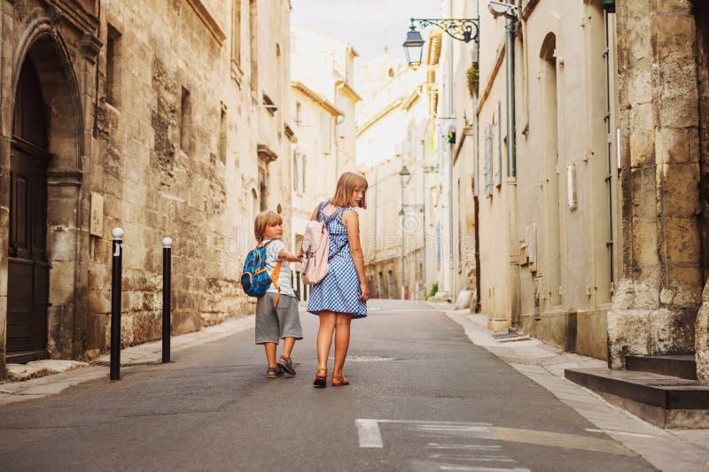Grupo de dos niños que caminan en las calles de la ciudad europea vieja fotografía de archivo