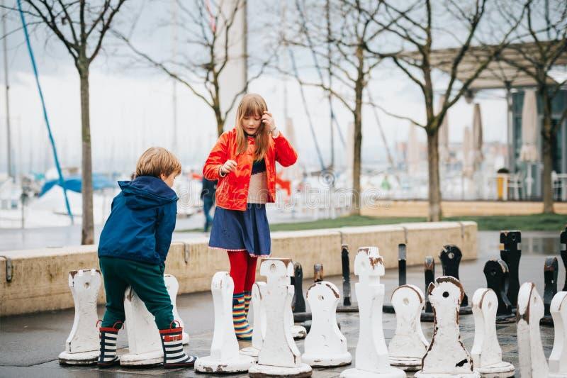 Grupo de dos niños que juegan a ajedrez gigante en patio fotos de archivo libres de regalías
