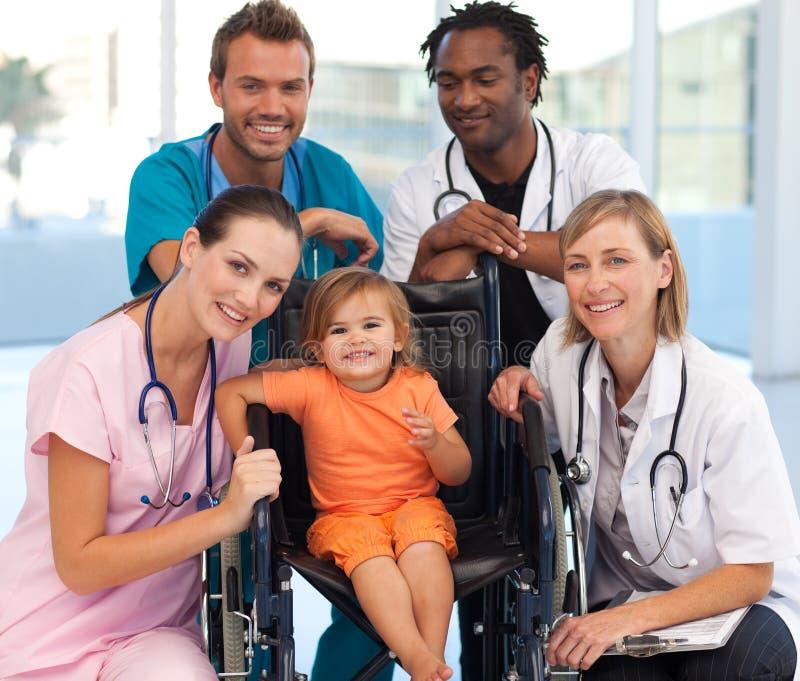 Grupo de doutores com um bebê em uma cadeira de rodas imagens de stock