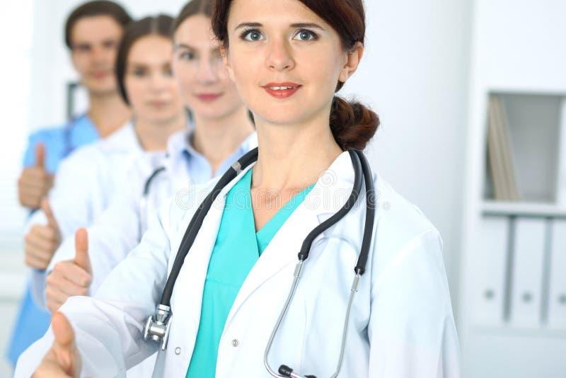 Grupo de doutores que mostram ESTÁ BEM ou de sinal da aprovação com polegar acima Nível elevado e serviço médico da qualidade, o  imagens de stock royalty free