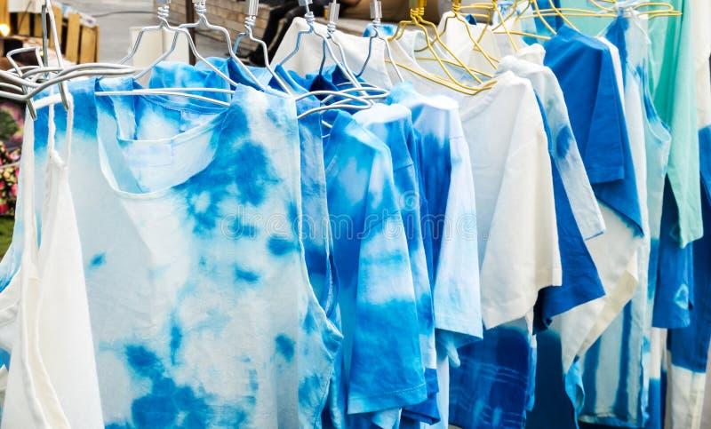 Grupo de ejecución azul y blanca del diseño de las camisetas del batik con la suspensión en el estante para la venta en el mercad imagen de archivo
