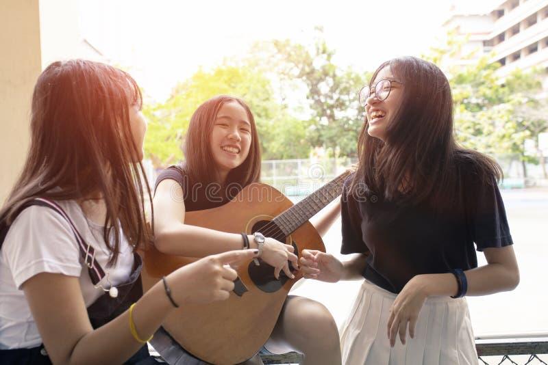 Grupo de emo??o asi?tica da felicidade do adolescente que joga a guitarra espanhola no lugar fotografia de stock