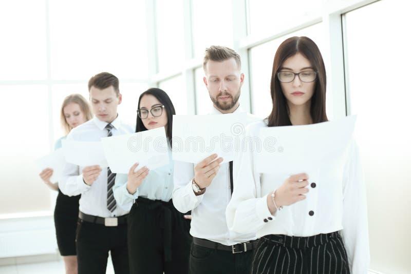 Grupo de empleados con los documentos que se colocan en fila foto de archivo